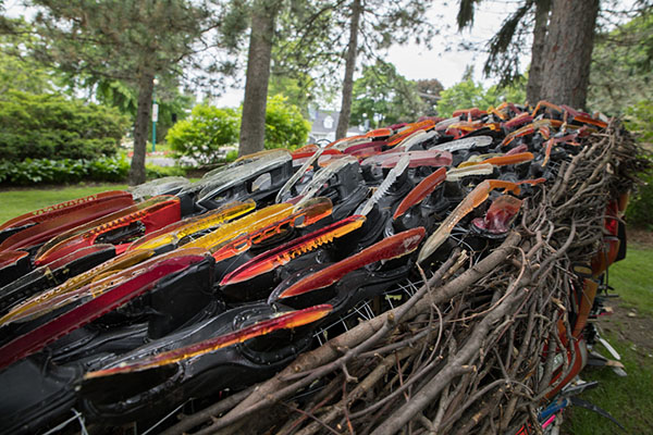 found hockey sticks sourced from Montreal community, found automotive tail lights, found branches, cast resin figure and hockey skate blades